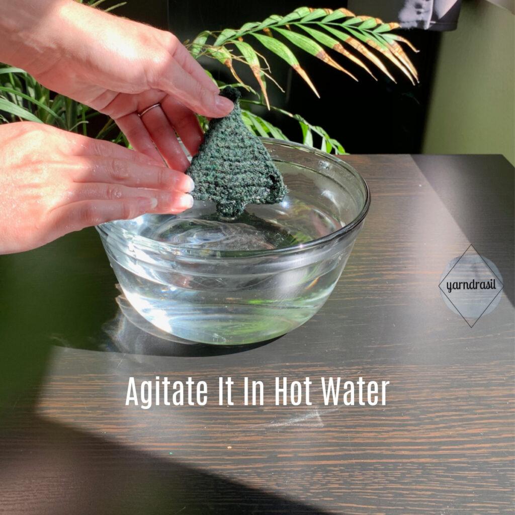 Agitate wool in hot water