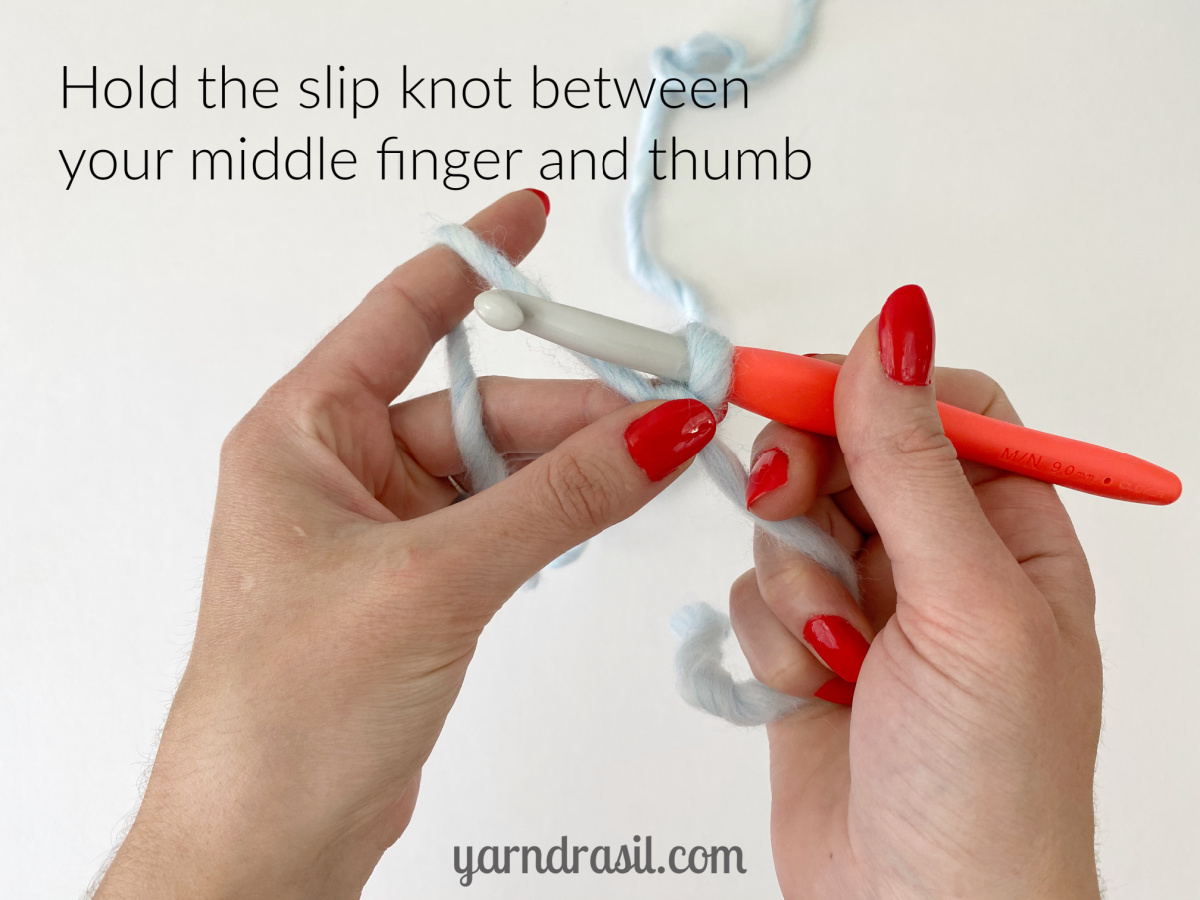 Hold the slip knot between your middle finger and thumb