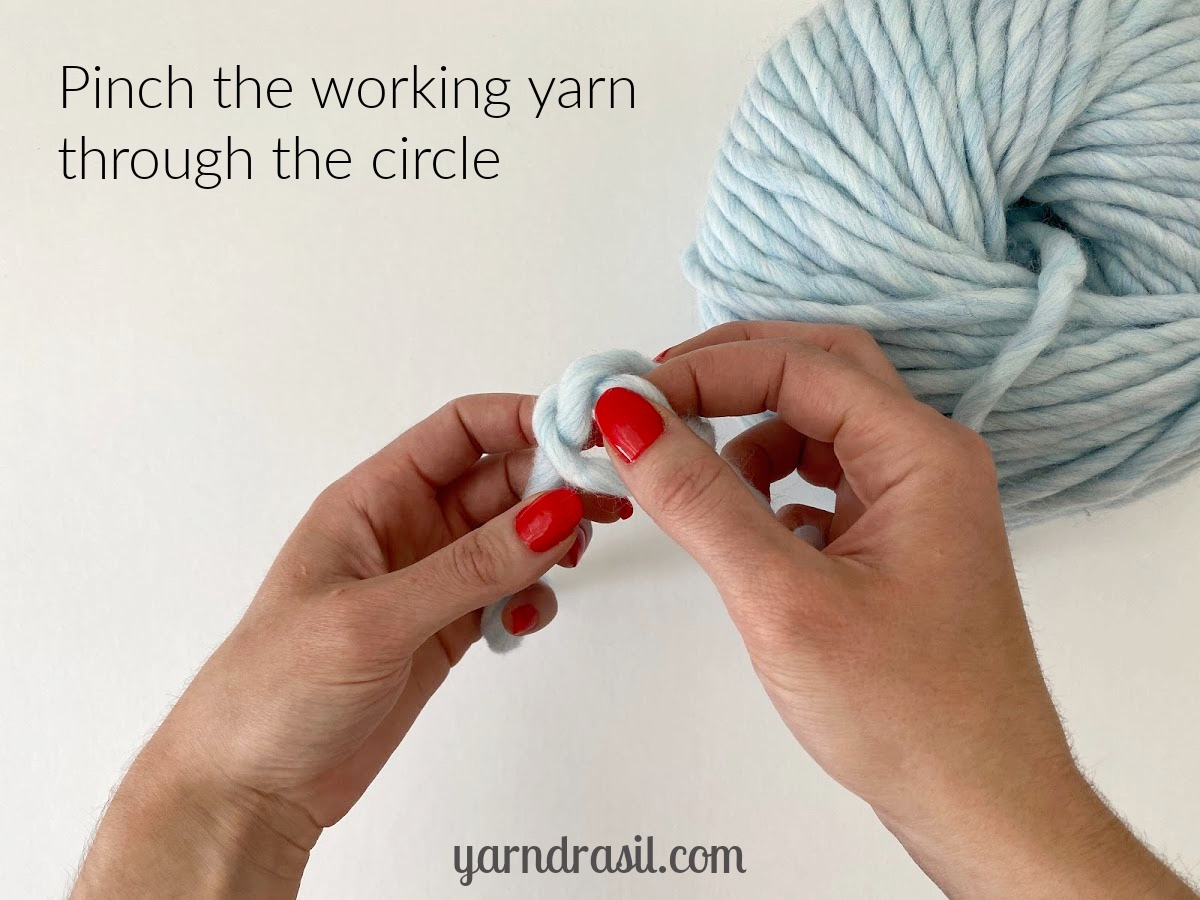 Pinch the working end of the yarn through the middle of the circle