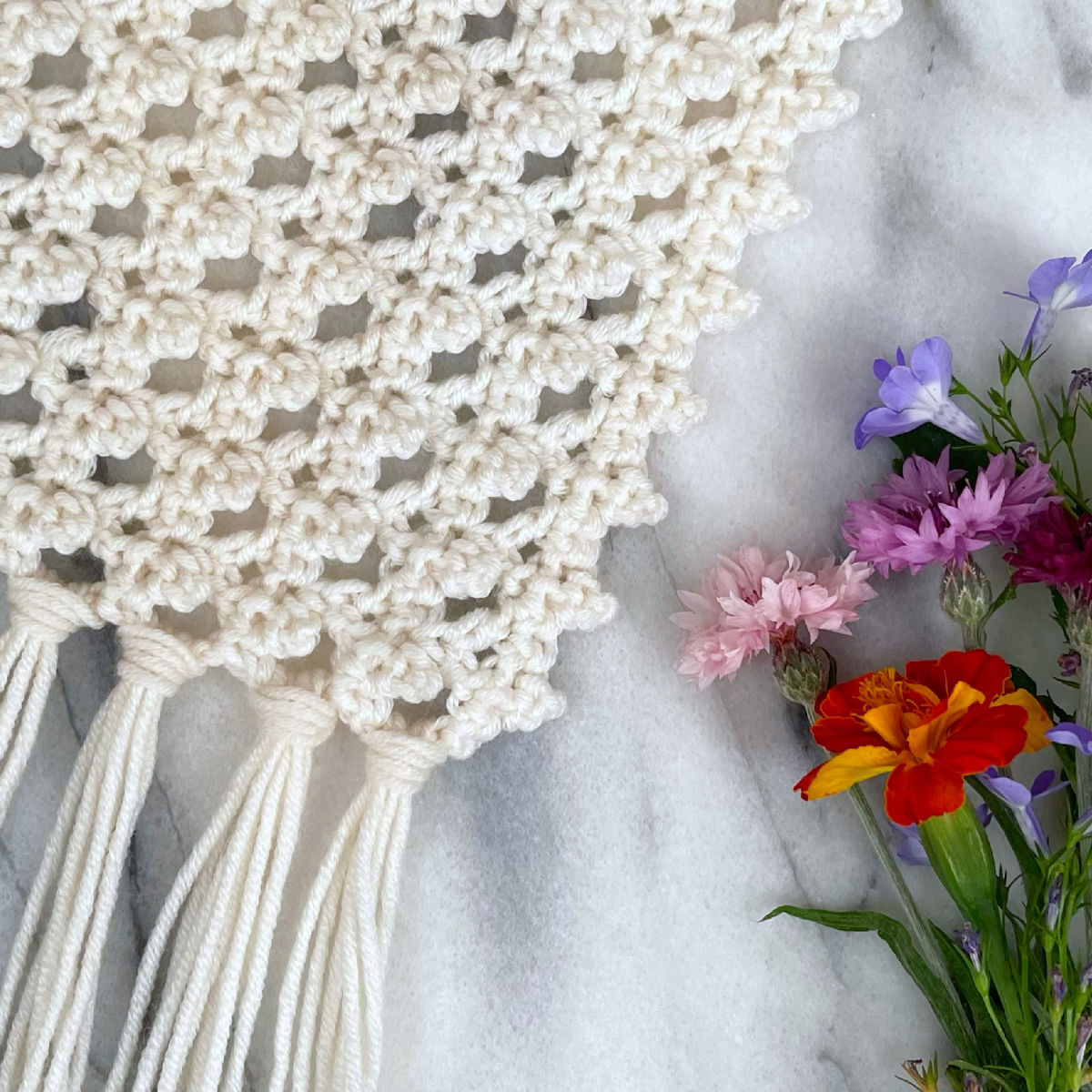 Close-up shot of flowers laying next to the shawl